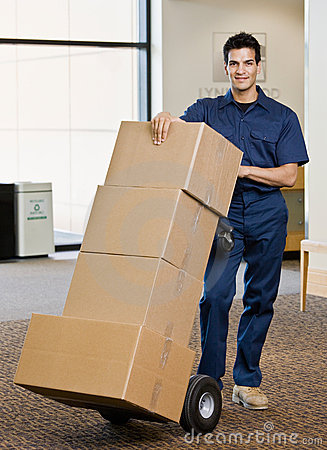 Free Delivery Man In Uniform Pushing Stack Of Boxes Stock Photography - 6604742