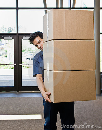 Delivery man in uniform carrying stack of boxes