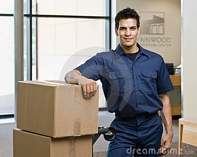 Delivery man in uniform posing with stack of boxes