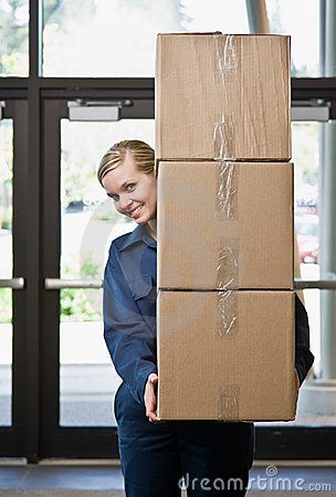 Delivery woman carefully carrying stack of boxes