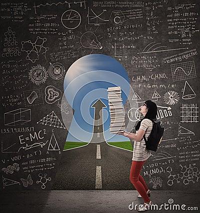 Den asiatiska kvinnliga studenten kommer med böcker med den framgångvägen och nyckelhålet