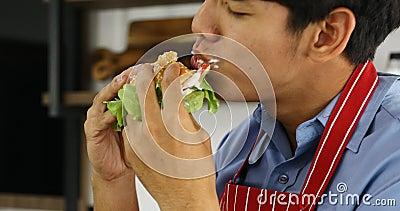 Den asiatiska mannen som äter hamburgaren, ser det läckert lager videofilmer
