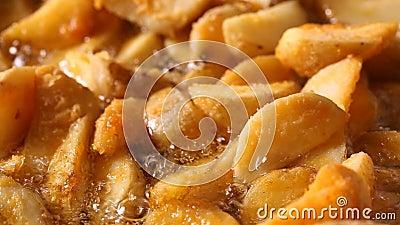 Den guld- stekte potatisen kilar att steka i varm kokande olja stock video