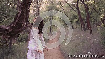 Den gulliga unga flickan i en vit genomskinlig lång klänning med en blom- modell och ett mörkt krabbt hår fångades av anden av stock video