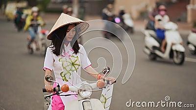 Den härliga flickan i den nationella klänningen Ao Dai och Lalocket sitter Non på en moped arkivfilmer