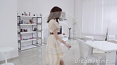 Den härliga unga kvinnan i en beige klänning flyttar sig i inre i vardagsrummet i ultrarapid Ultrarapidfamiljhem stock video