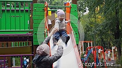 Den kaukasiska småbarnspojken som har kul att glida ner våt metallglidning på lekplats i stadsparken efter regn i lager videofilmer
