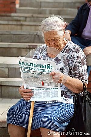 Den äldre kvinnan läser tidningen i service av Alexei Navalny Redaktionell Arkivfoto
