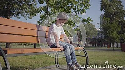Den ledsna ensamma pysen som sitter på bänken i, parkerar Gulligt barn som utomhus spenderar tid bara Sommartidfritid stock video