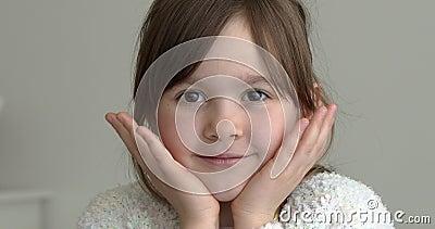 Den lilla flickan står hemma och tittar på kameran med ett fint leende stock video