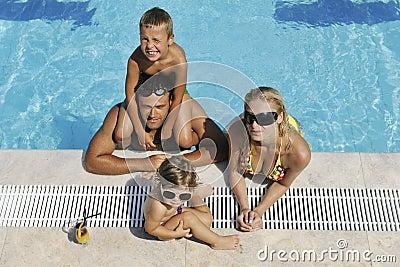Den lyckliga unga familjen har gyckel på simbassäng