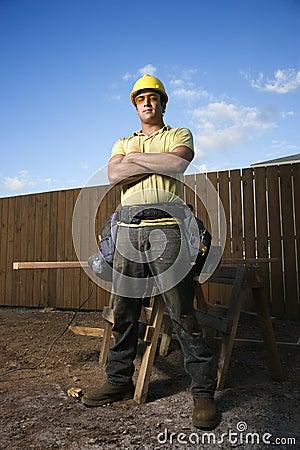 Den Male byggnadsarbetaren plattforer med vikta armar