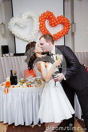 Den romantiska den kyssbruden och brudgummen i bröllop ge en bankett för