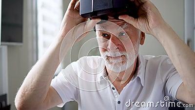 Den snygga stiliga höga mannen i vit tar av VR 360 hemmastadda exponeringsglas Aktivt äldre folk arkivfilmer