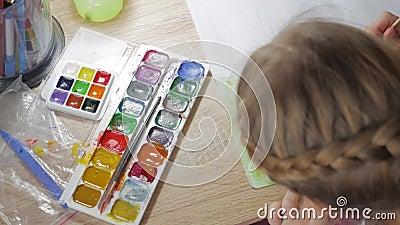 Den tonårs- flickan är hemma förlovad i kreativitet, drar vattenfärgen på en tabell i rum Barn som drar bästa sikt artistically arkivfilmer