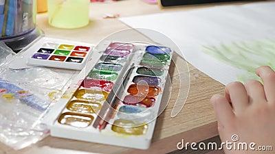 Den tonårs- flickan är hemma förlovad i kreativitet, drar vattenfärgen på en tabell i rum Barn som drar bästa sikt artistically stock video