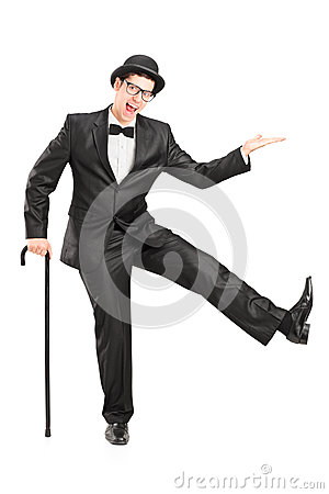 Den unga aktören i svart passar innehav en rotting och en dans