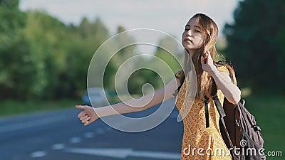 Den unga härliga flickan med långt hår i en klänning och en ryggsäck på henne fångar tillbaka en bil på motorvägen Hon visar a stock video