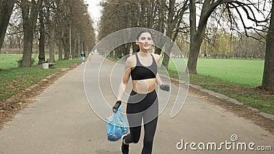 Den unga idrotts- flickan i en svart sportdräkt och handskar kör till och med grön sommar parkerar med en avfallpåse i hennes han lager videofilmer