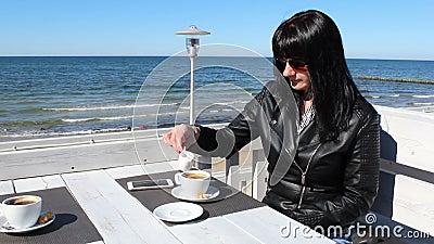 Den unga kvinnan som rör kaffe med en tesked i utomhus- hälla för cafeyoungkvinna, mjölkar i kaffe i ett utomhus- kafé arkivfilmer