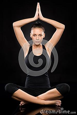 Den unga kvinnan som utför yoga med lyftt, räcker