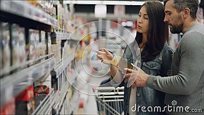 Den unga kvinnan väljer te i matlager, hjälper hennes make och son henne som ser produkter och samtal buying arkivfilmer
