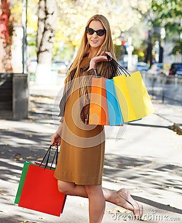 Den unga lyckliga kvinnan med shopping hänger lös