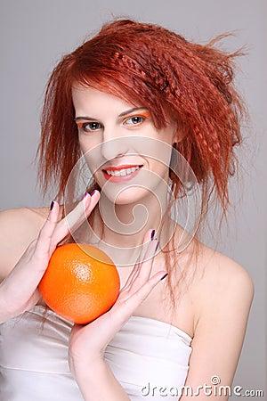 Den unga redhaired kvinnan med apelsinen i henne räcker