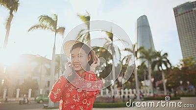 Den vietnamesiska flickan sätter på en nationell La för lock Non i strålarna av aftonen arkivfilmer