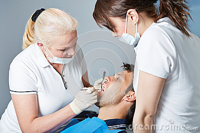 Dental assistant watching dentist at work