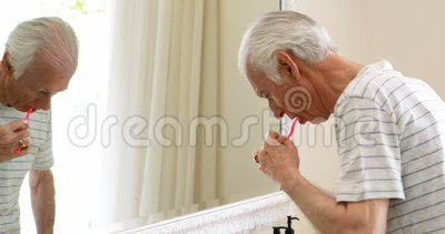 Dentes de escovadela do homem superior com a escova de dentes no banheiro filme