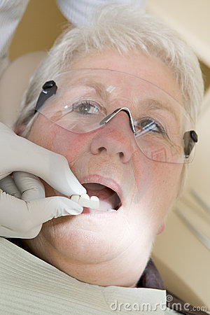 Dentist in exam room fitting dentures on woman