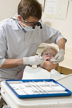 Dentist in exam room with woman