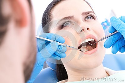 Dentist examines the teeth of the patient