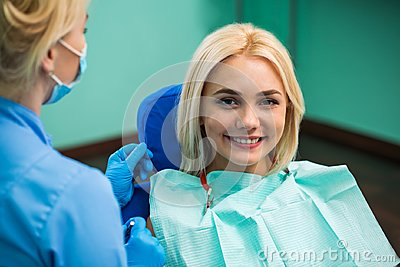 Dentist and happy smiling blonde woman. Work of stomatologist with patient. Make your smile perfect. Stock Photo
