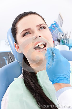 Dentist is looking for the defects in oral cavity