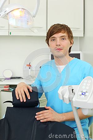 Dentist looks at camera in dental clinic