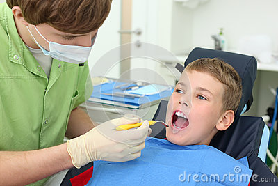 Dentist looks at teeth of boy in dental clinic