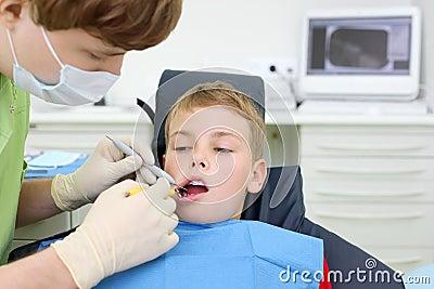 Dentist looks at teeth of boy in dental clinic