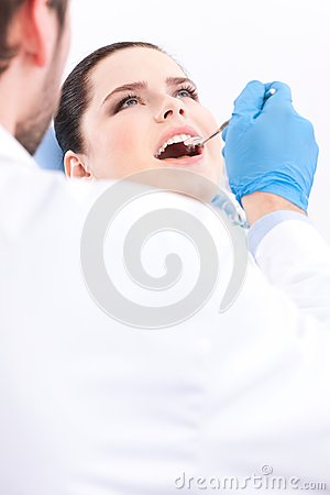 Dentist in medical gloves examines the oral cavity