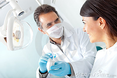 Dentist showing how to brush teeth
