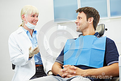 Dentist talking with patient on chair