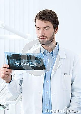 Dentist thinks over the roentgenogram