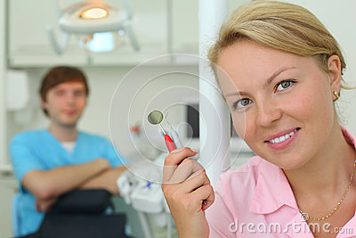 Dentist with tools in cabinet of dental clinic