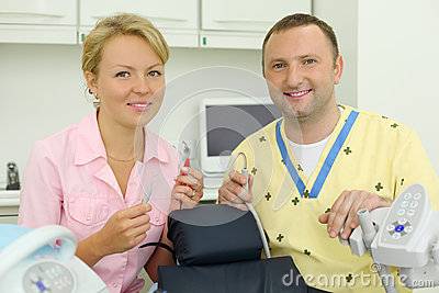 Dentists hold tools near chair for patient