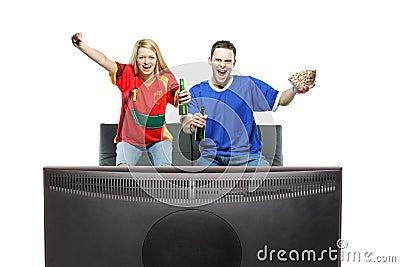 Deporte de observación emocionado del hombre y de la mujer en una TV