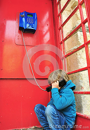 Depressed boy in telephone box