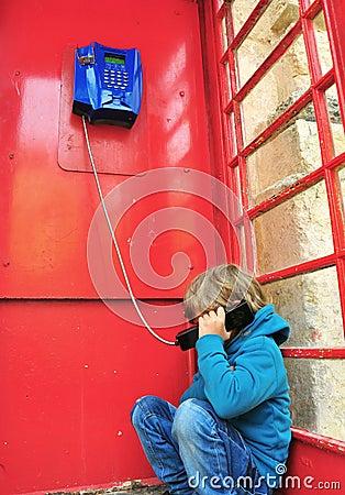 Depressed boy in telephone box