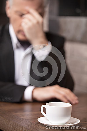 Depressed businessman. Depressed mature businessman sitting at t