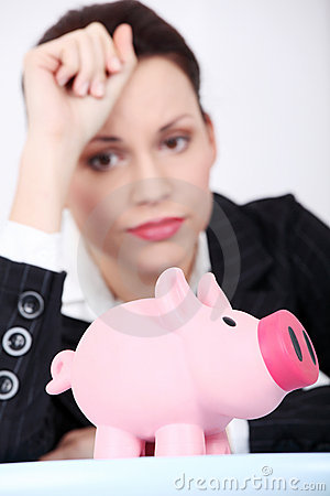 Depressed businesswoman looking at her piggy bank.